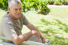 Thoughtful mature man sitting on park bench Royalty Free Stock Photography