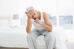 Thoughtful mature man yawning in bed Stock Images