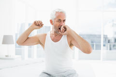 Thoughtful mature man yawning in bed Stock Photos