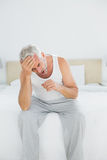 Thoughtful mature man yawning sitting in bed Stock Photo