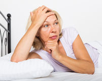 Thoughtful mature woman   in bedroom Stock Photos