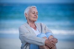 Thoughtful mature woman day dreaming. On the beach royalty free stock photo