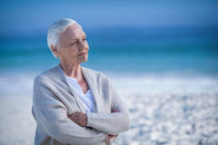 Thoughtful mature woman day dreaming. At the beach stock photography