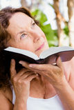 Thoughtful mature woman holding bible Royalty Free Stock Photos