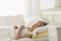 Thoughtful Mature Woman Lying On Bed Royalty Free Stock Photos