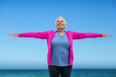 Thoughtful mature woman outstretching her arms Royalty Free Stock Image
