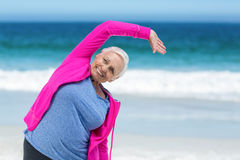 Thoughtful mature woman outstretching her arms Royalty Free Stock Photography