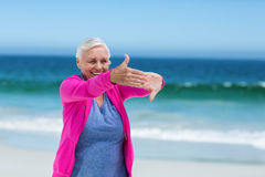 Thoughtful mature woman outstretching her arms Royalty Free Stock Images