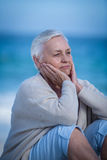 Thoughtful mature woman sitting on the sand Royalty Free Stock Image