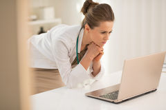 Thoughtful medical doctor woman looking in laptop Royalty Free Stock Images