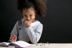 Thoughtful metis girl is doing sums stock photo