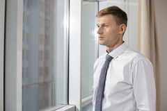 Thoughtful mid adult businessman looking through window at home Royalty Free Stock Photography