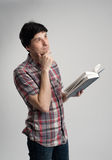 Thoughtful mid adult man with book Stock Image