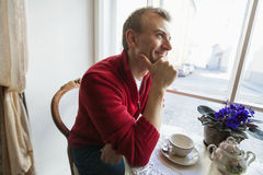 Thoughtful mid adult man sitting at table in cafe Royalty Free Stock Photos