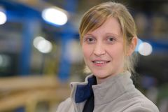 Thoughtful middle age woman smiling in warehouse. Thoughtful middle age women smiling in a warehouse Royalty Free Stock Images