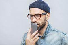 Thoughtful middle aged male with stubble holds smart phone near mouth, being deep in thoughts, thinks about future plans, isolated stock image