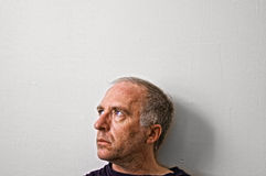 Thoughtful middle aged man. Side portrait of thoughtful middle aged man in white background with copy space Royalty Free Stock Photo