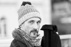 Thoughtful middle aged man looking at you with calmness. Portrait of stylish middle aged bearded man wearing woolly hat and being thoughtful while looking at you royalty free stock photography