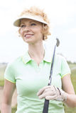 Thoughtful middle-aged woman looking away while holding golf club Stock Image
