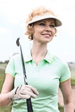 Thoughtful middle-aged woman looking away while holding golf club. Thoughtful middle-aged women looking away while holding golf club stock images