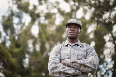 Thoughtful military soldier standing with arms crossed. In boot camp Royalty Free Stock Photography