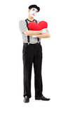 Thoughtful mime artist holding a red heart Royalty Free Stock Photography