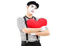 Thoughtful mime artist holding a red heart Stock Photo