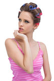 Thoughtful model in hair curlers posing and looking away Royalty Free Stock Image