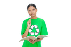 Thoughtful model wearing recycling tshirt holding notebook Royalty Free Stock Image