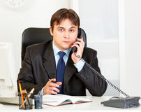 Thoughtful modern business man talking on phone Stock Images