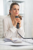 Thoughtful modern business woman holding phone Royalty Free Stock Images