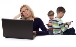 Thoughtful mother with laptop and kids with tablet computers Royalty Free Stock Images
