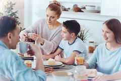 Thoughtful mother taking care of family during breakfast. Mothers heart is healing. Selective focus on a mindful mom pouring black tea into a cup for her little Stock Photography
