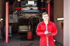 Thoughtful motor mechanic standing making notes Stock Photo