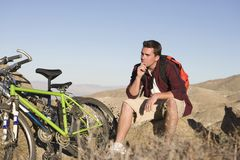 Thoughtful Mountain Biker Sitting On Rock Royalty Free Stock Photo