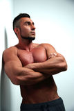 Thoughtful muscular man with arms folded Royalty Free Stock Images