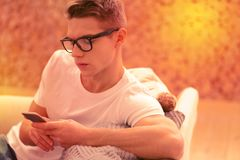 Thoughtful musing guy waiting for response on message. Bad news. Meditative pensive guy toying on phone and wearing glasses royalty free stock photos