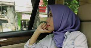 Thoughtful muslim woman in the car stock video footage