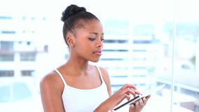 Thoughtful natural model using her tablet computer stock video