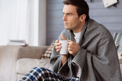 Thoughtful nice man holding a cup of tea Royalty Free Stock Photos