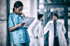 Thoughtful nurse examining medical report. In hospital Stock Images