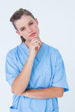 Thoughtful nurse looking at camera with hand on chin Royalty Free Stock Image