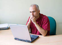 Thoughtful office worker. Working at the desk with laptop stock photo
