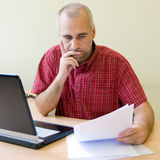 Thoughtful office worker. Working at the desk with sale report stock photo