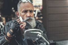 Thoughtful old bearded man shaving. Attentive mature biker is sitting on motorcycle and using his knife in order to shave cheek. He looking at mirror with Royalty Free Stock Photo