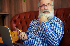 Thoughtful old man holding smartphone Stock Images