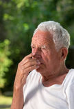 Thoughtful old man in park Stock Image