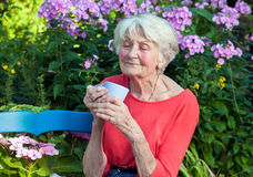 Thoughtful Old Woman with Coffee at the Garden Stock Photography