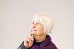 Thoughtful old woman looking up Stock Photos