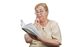Thoughtful old woman reading, head leaning on hand Royalty Free Stock Image